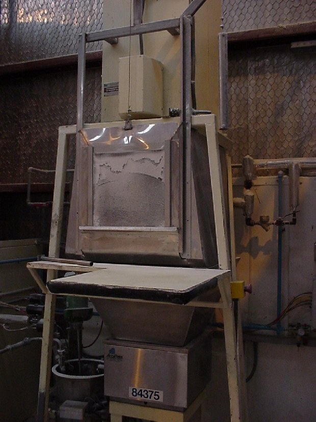 Debagging station.  The perspex cover is lifted, bag inserted, slit open and emptied into the auger hopper.  Dust is carried away into the intergral dust colletor which shakes any collected powder into the hoppper after the cover is closed.  The dust collector only operates when the cover is open.